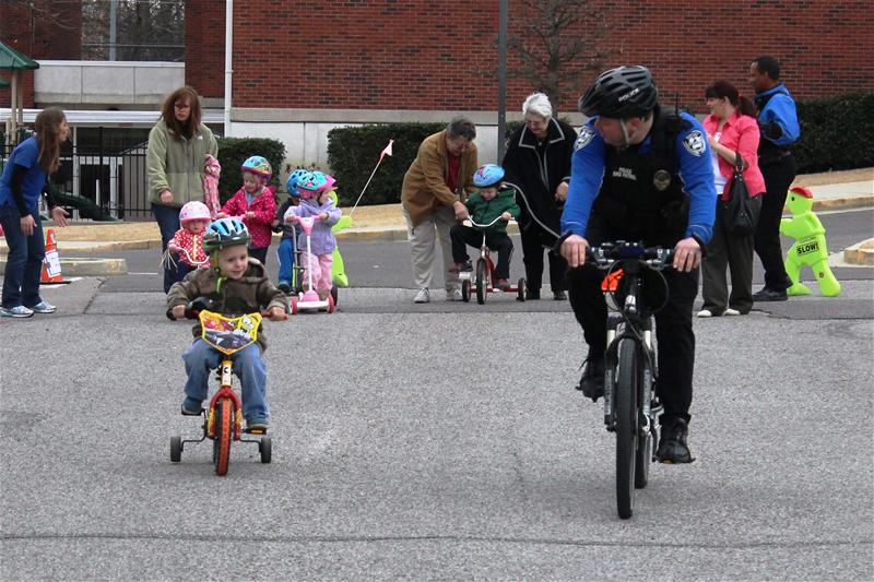 Officer on a bike riding next to a child