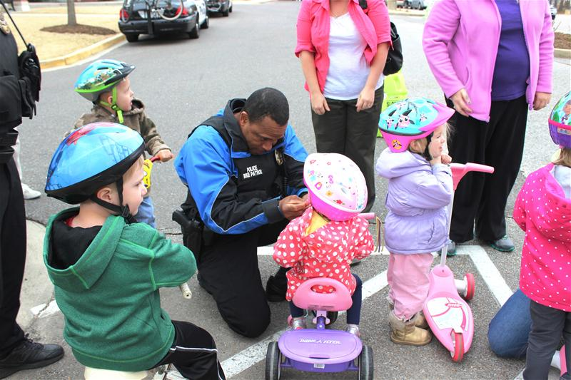 Officer adjusting a child's bike helmet