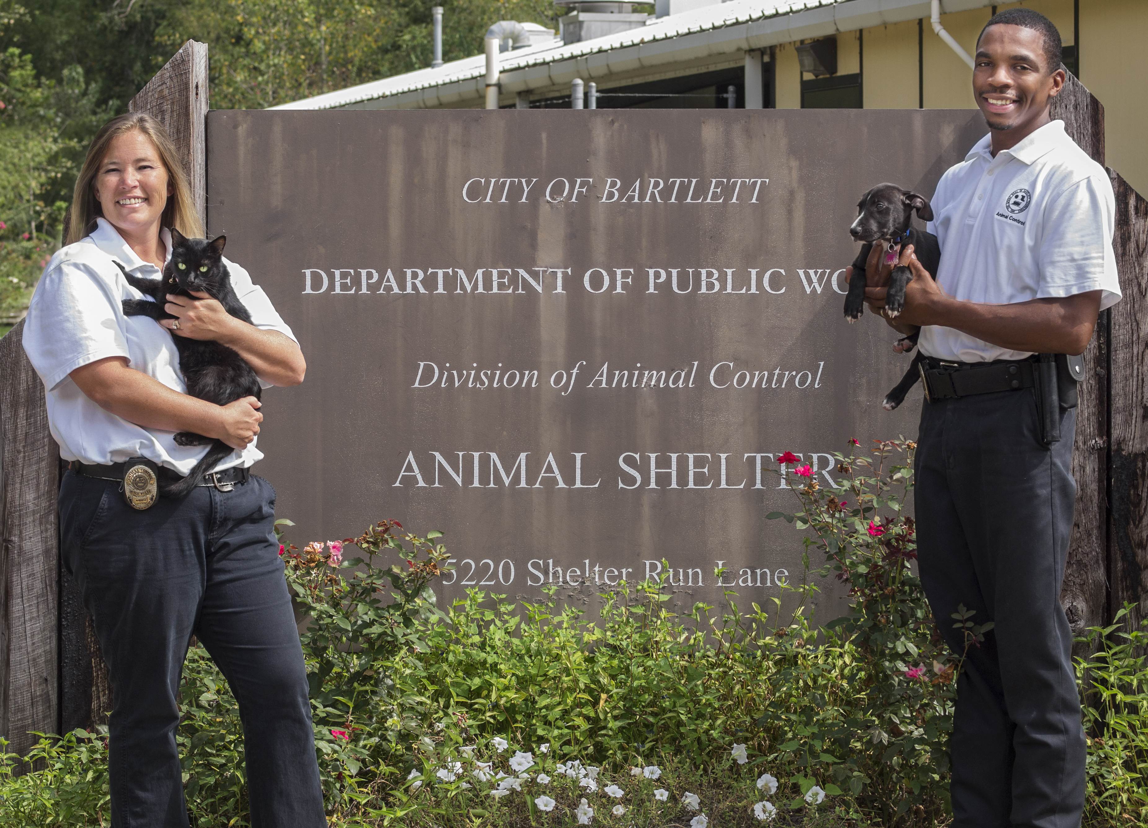 Two Animal Control Officers Holding a Cat and Dog